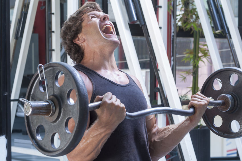Man lifting barbell focusing biceps and screaming of heaviness