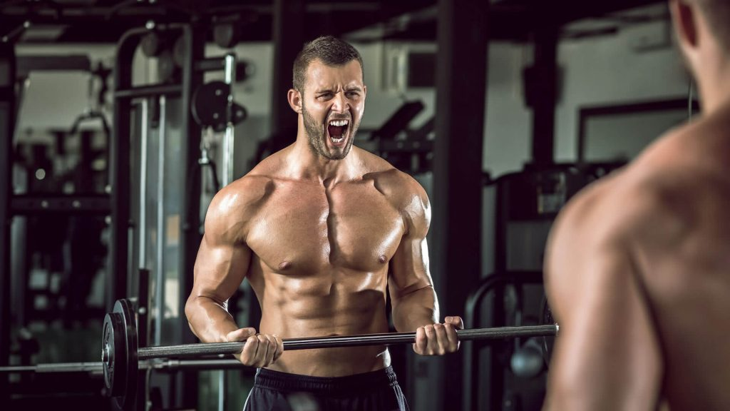 Man lifting barbell looking in front of a mirror