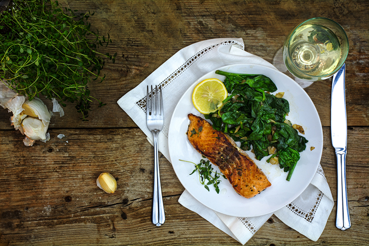 A plate of fish fillet, leafy veg and a slice of lemon set on a table, low-carb