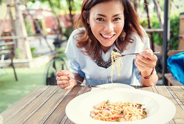 Ketogenic, Girl eating pasta on outdoor table
