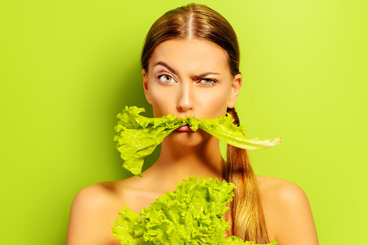 Vegan diet, close up, lady with leafy vegetable on her mouth