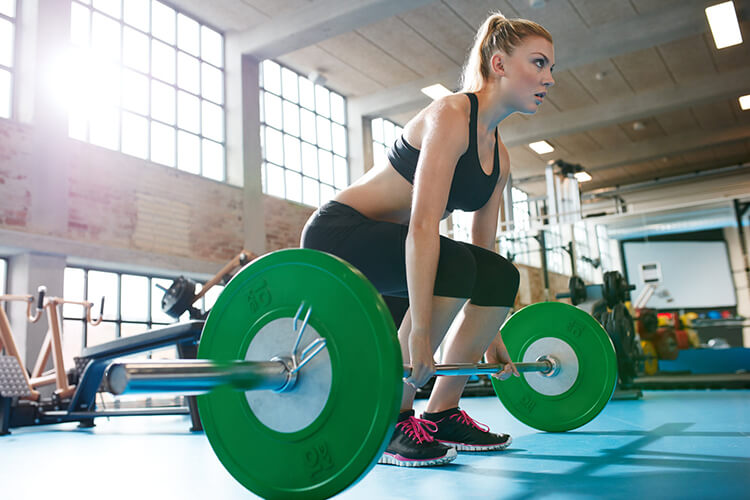 Woman preparing to lift the green barbell, powerlifting woman