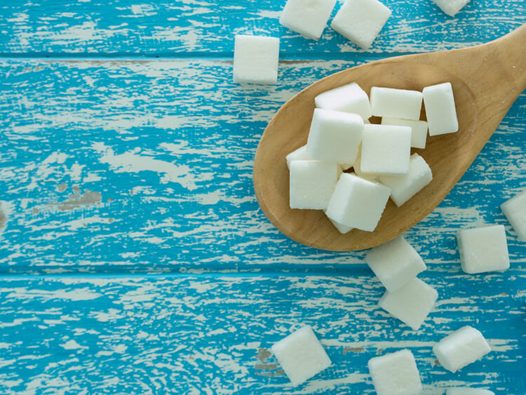 Closeup top view sugar cubes on wooden spoon on white blue wooden table , sugar myth, sugar causes cancer