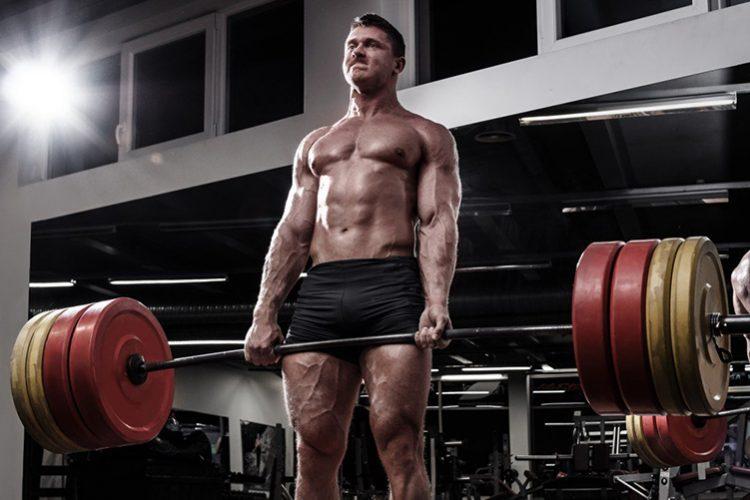 man deadlifting looking in front of a mirror