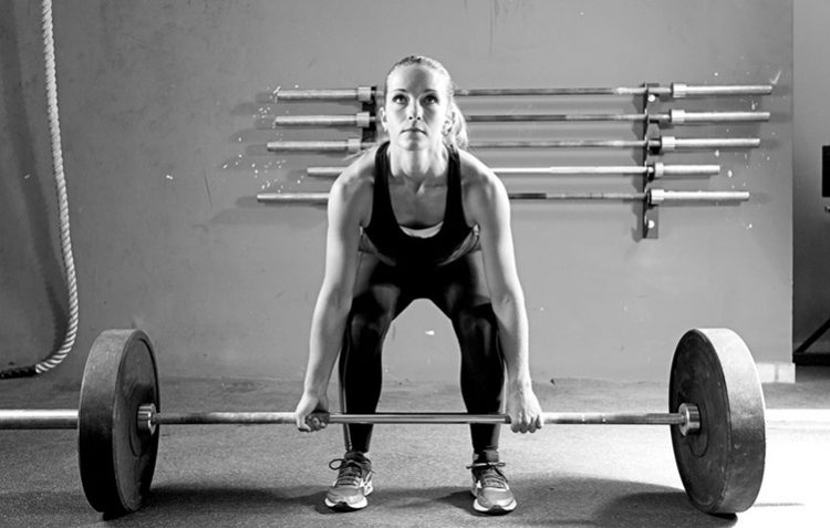 female athlete is preparing to lift deadlift at the crossfit box - focus on the woman, deadlift
