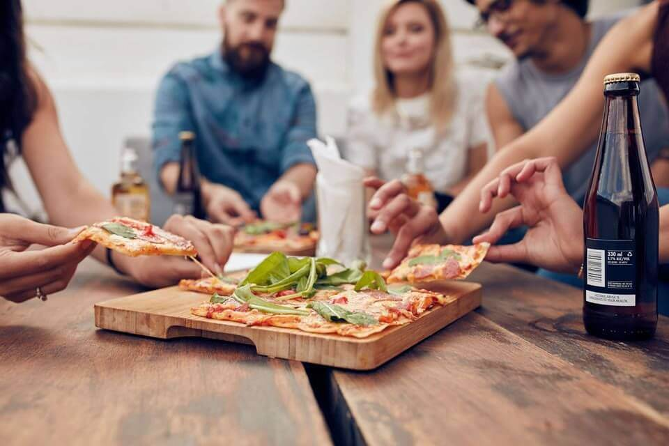 A group of friends enjoying a pizza on the table, eating addiction