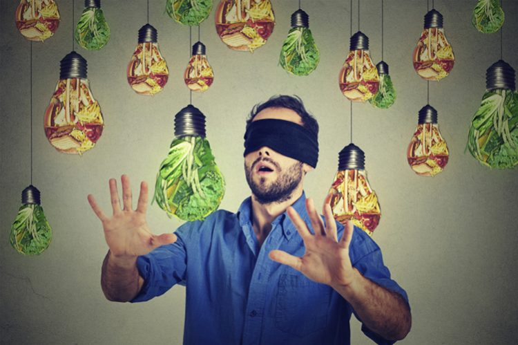 Blindfolded young man walking through light bulbs shaped as junk food and green vegetables isolated on gray wall background, food addictiond addiction