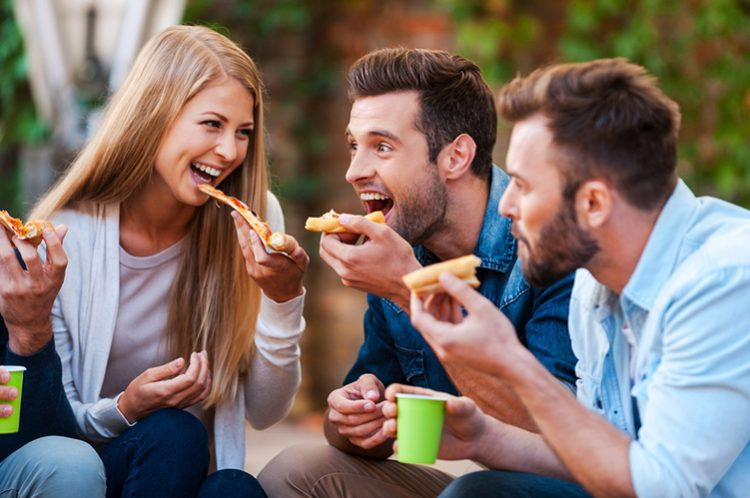a lady and 2 men enjoys eating pizza outdoor, food addiction