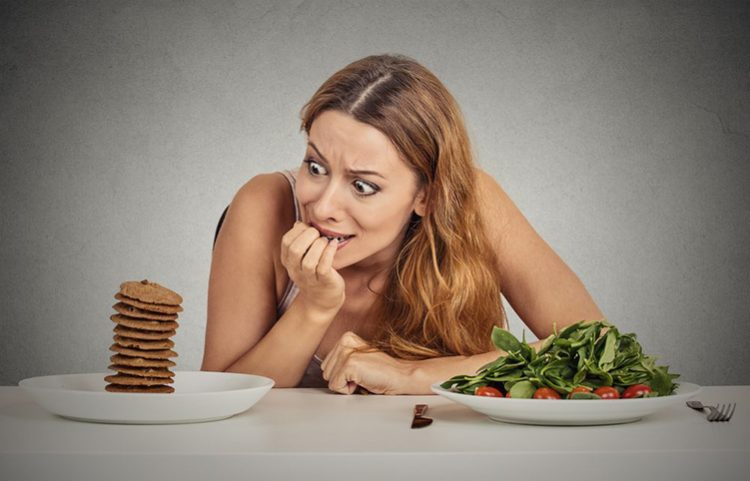 lady is more tempted to eat the pancake than the salad that are on the table, food addiction