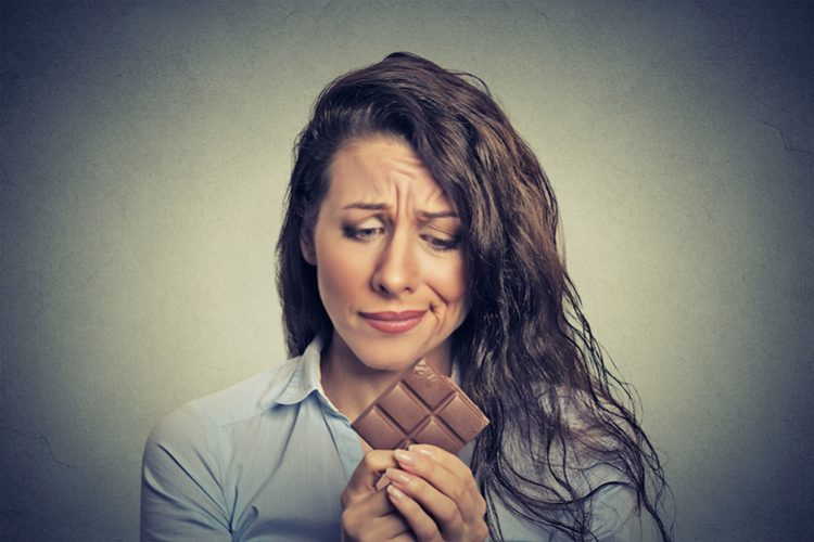 Sad woman craving for a chocolate on her hand islolated in grey background, food addiction
