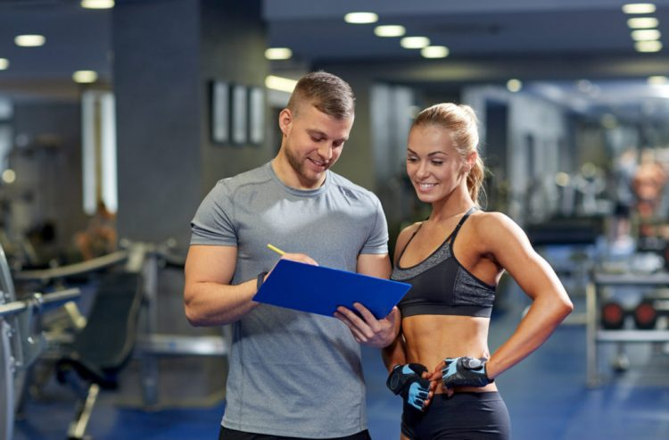smiling young woman with personal trainer in gym, recovery