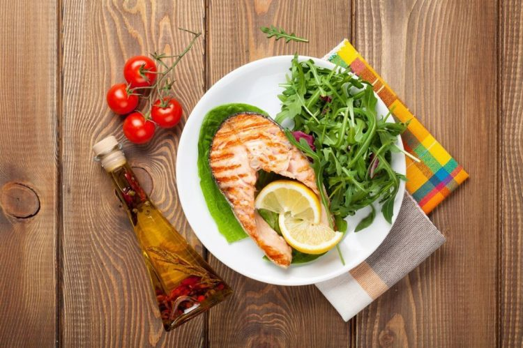 grilled fish and green veggies with slice of lemon on white plate, top view of food on a wooden table, recovery