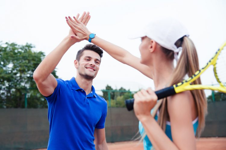 Male and female tennis players gives five at the tennis court after a match, recovery