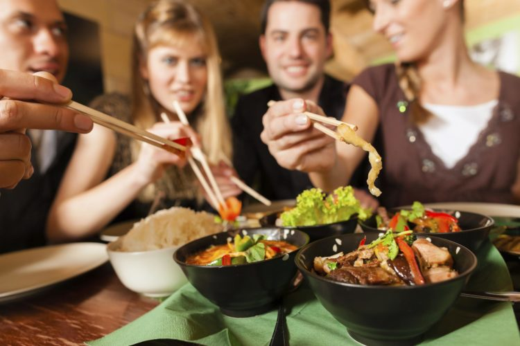 Young people eating in Thai restaurant, intermittent fasting