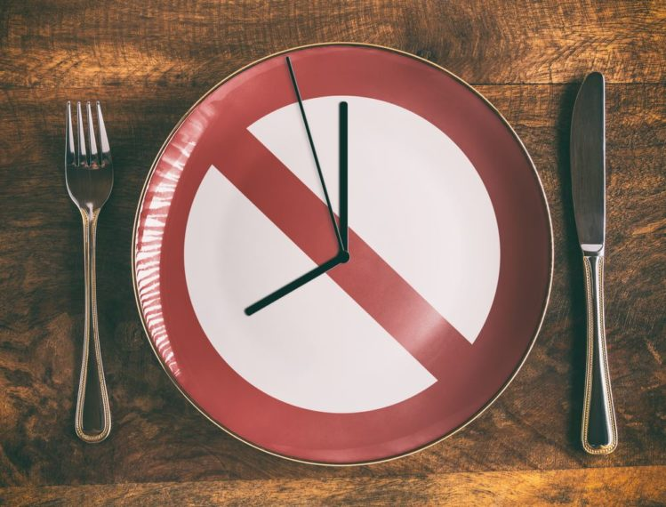 Clock like plate on the table with fork and bread knife, intermittent fasting