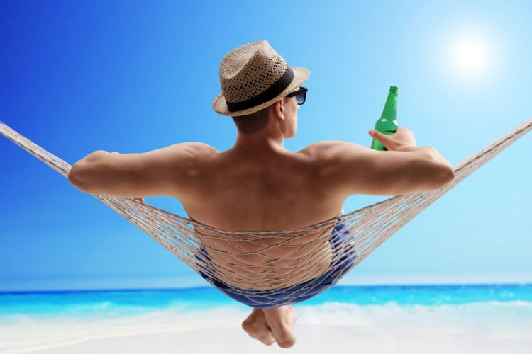 back view of a man sitting on a hammock with beer on the beach, weight loss