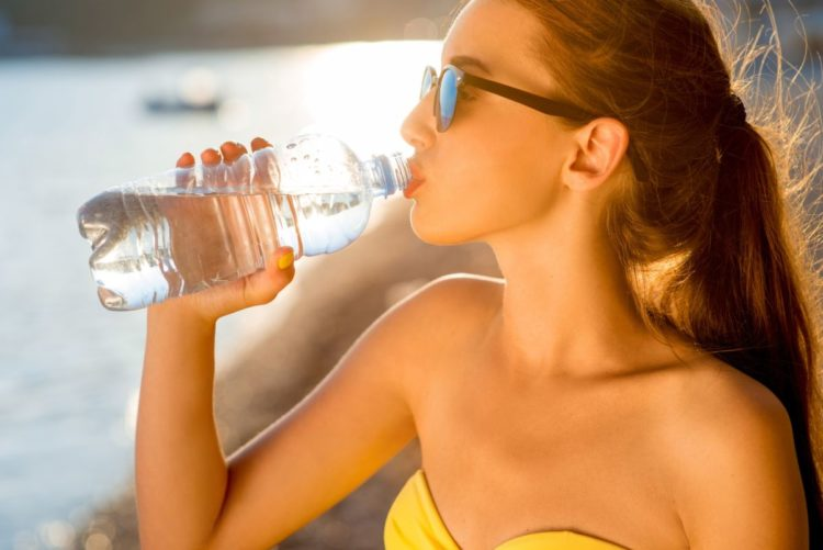close up view of a lady with sunglasses drinking bottled water at the beach, weight loss