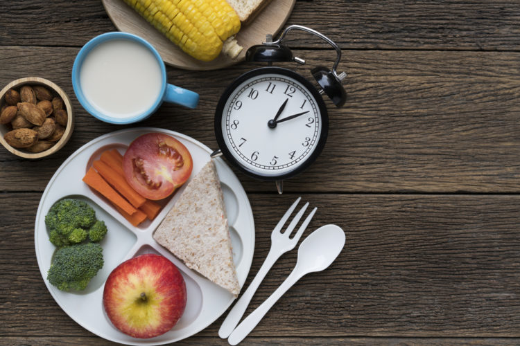 a plate of a heathy food, a cup of milk and an alarm clock on a wooden table,