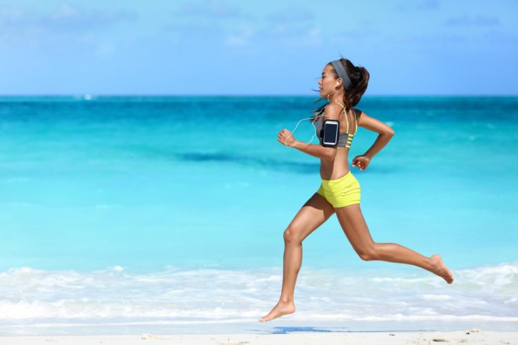 Young lady running on a beach at the seaside, weight loss