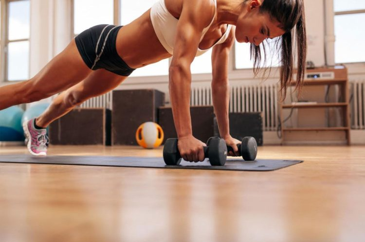 Woman doing push-up exercise with dumbbell, weight loss