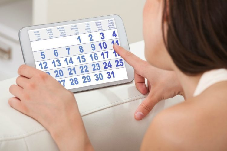 side view of a lady checking the calendar on her tablet, Menstrual cycle