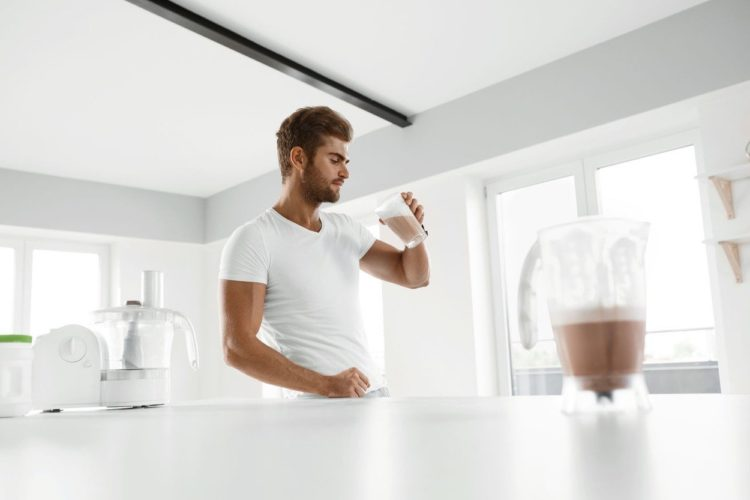 Muscular Man With Strong Muscles Drinking Protein Shake In Kitchen, Best Supplements