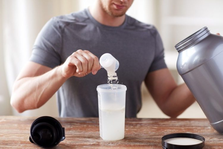 Muscular man putting a spoonful of food supplement on plastic bottle, best supplements