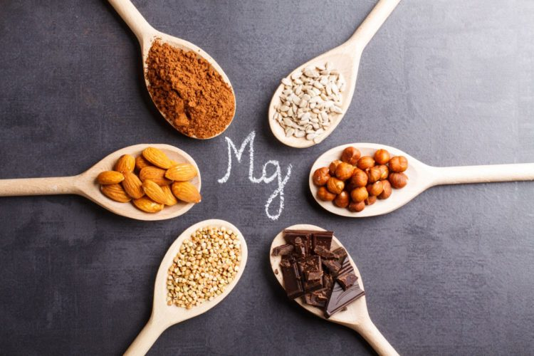 6 spoonful of grains, nuts and cocao flakes rich in magnesium arranged in the table with caption Mg written at the center, best supplements