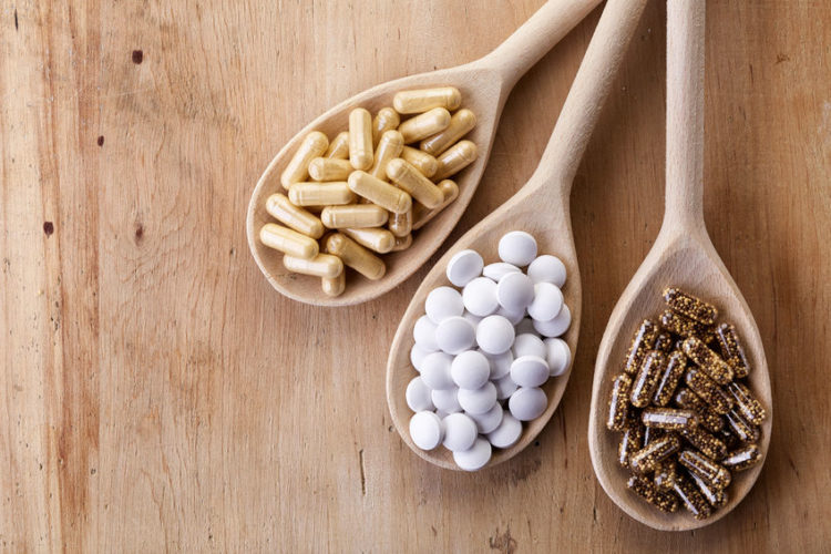 wooden spoons of various dietary supplements on wooden background. best supplements