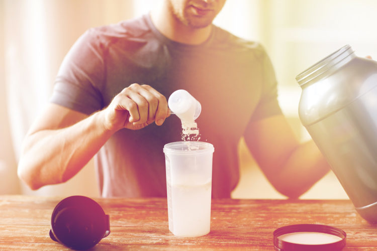 close up of man with jar and bottle preparing protein shake, useless supplements